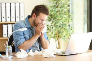 Employee Sneezing into Kleenex Because Office Needs an Air System Cleaning
