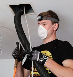 Man on Ladder Performing Duct Cleaning Services